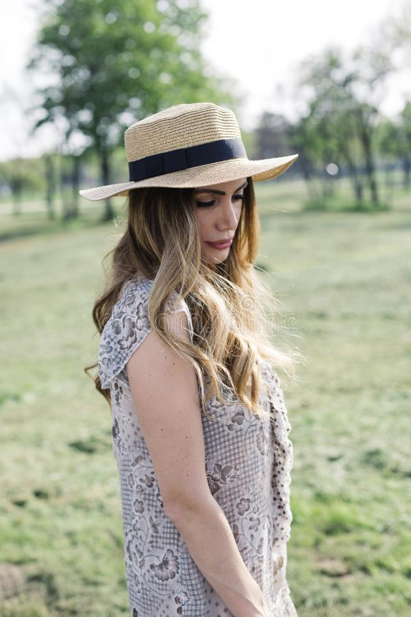 一名美丽的端庄的妇女的画象有摆在同水准的帽子的 免版税库存图片