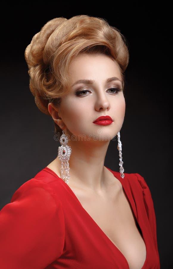 一名美丽的端庄的妇女的画象一件红色礼服的 免版税库存照片