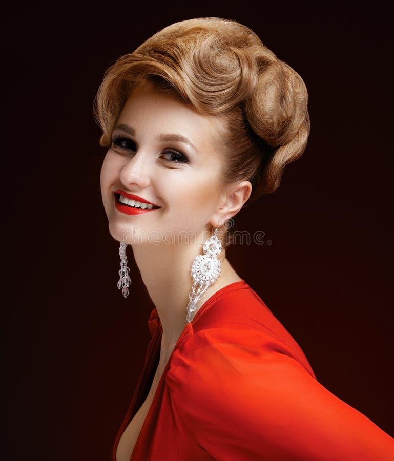 一名美丽的端庄的妇女的画象一件红色礼服的 图库摄影