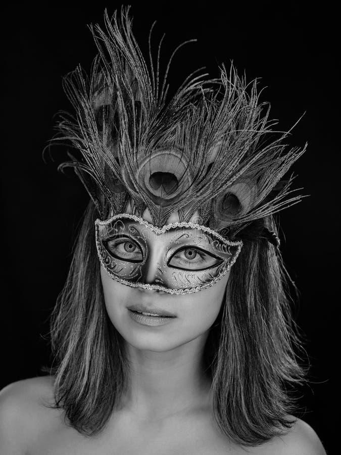 一名美丽的绿眼的妇女的黑白特写镜头画象一个威尼斯式狂欢节面具的 库存图片