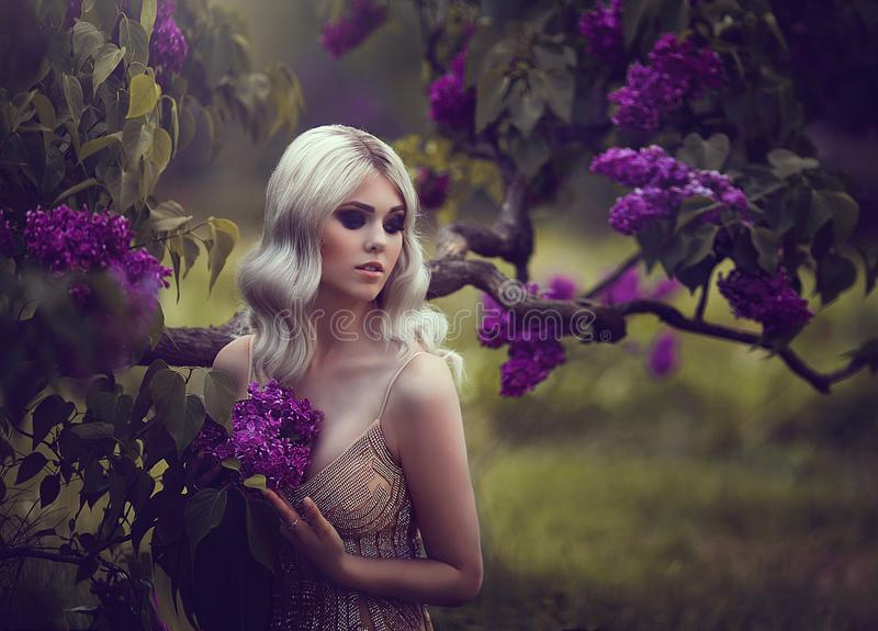 一名美丽的肉欲的年轻白肤金发的妇女的画象在春天 开花的日庭院可能反弹晴朗 金礼服的女孩 库存照片