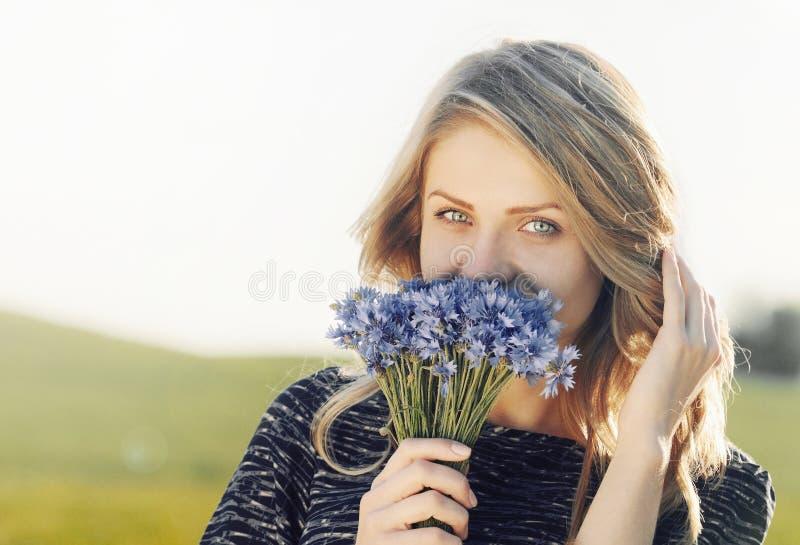 一名美丽的年轻快乐的妇女的画象有矢车菊的 库存图片