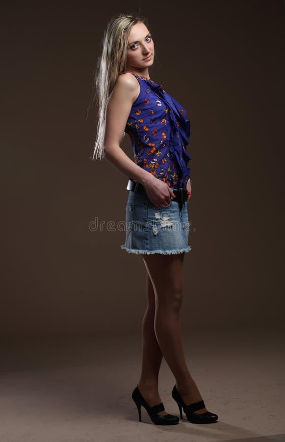 一名美丽的年轻成人亭亭玉立的性感和可爱的淫荡相当白肤金发的妇女的画象蓝色高雅时兴的短裤的 库存照片