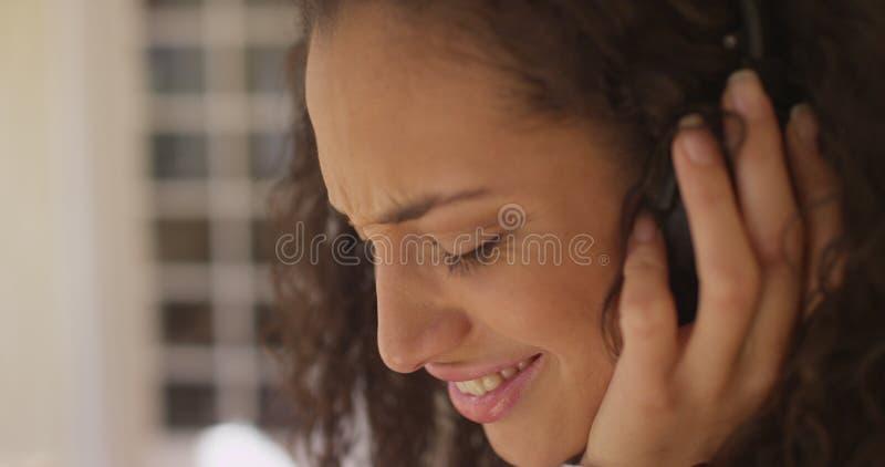 一名美丽的年轻拉丁美州的妇女佩带的耳机的特写镜头 免版税图库摄影