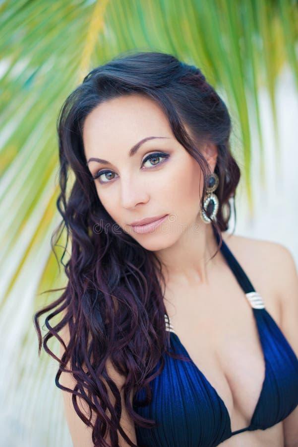 一名美丽的年轻深色的妇女的画象有长的卷发的反对异乎寻常的自然背景  免版税库存图片