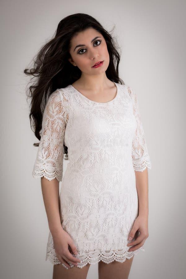 一名美丽的年轻深色的妇女的画象白色礼服的 免版税库存图片