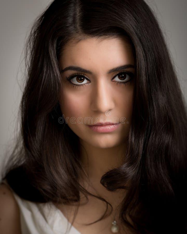 一名美丽的年轻深色的妇女Lookng的画象Camer的 库存照片