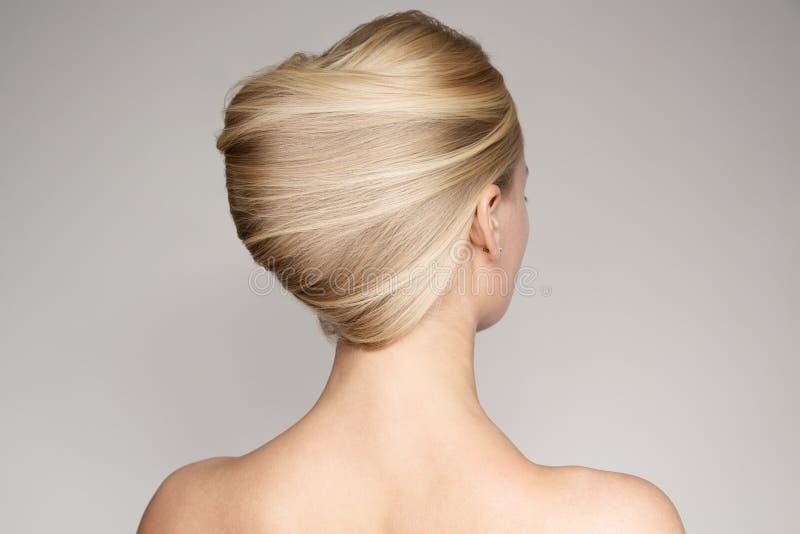 一名美丽的年轻白肤金发的妇女的画象有壳发型的 免版税库存图片