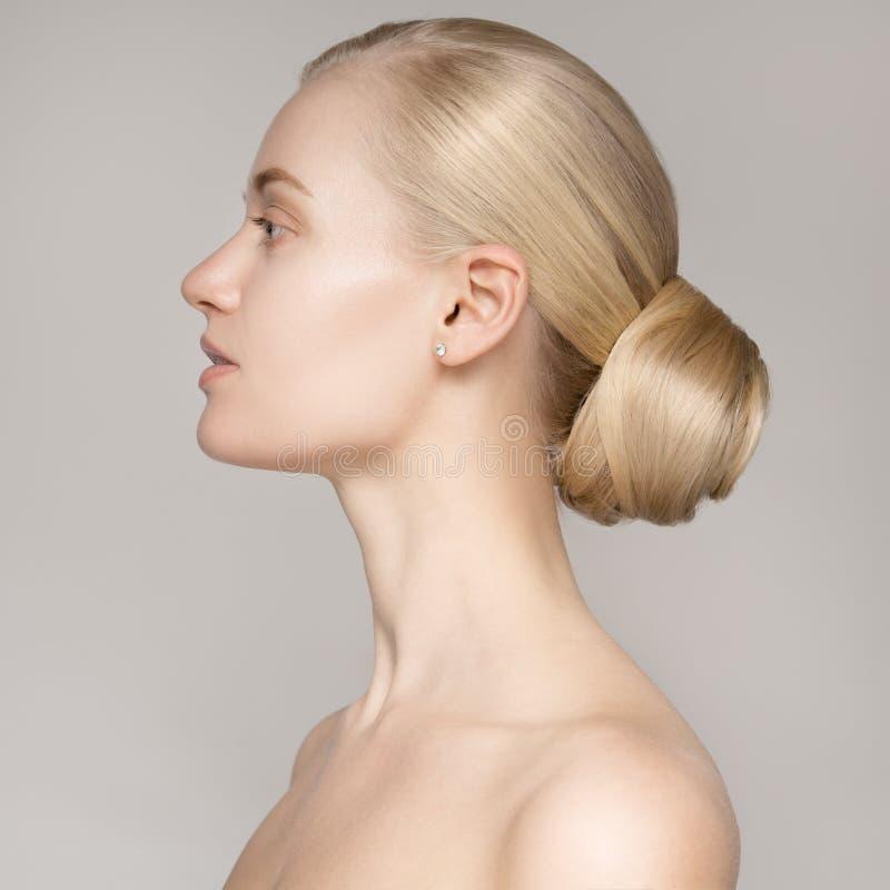 一名美丽的年轻白肤金发的妇女的画象有小圆面包发型的 免版税库存照片