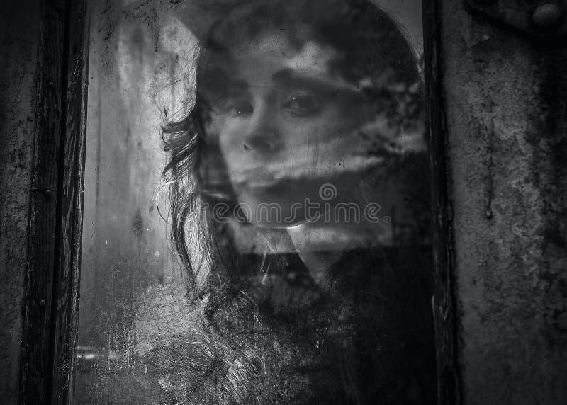 一名美丽的年轻鬼的妇女的艺术画象,神色通过难看的东西称呼了窗口。 库存图片