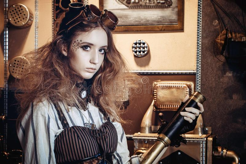 一名美丽的steampunk妇女的画象,有在g的一台望远镜的 免版税库存照片