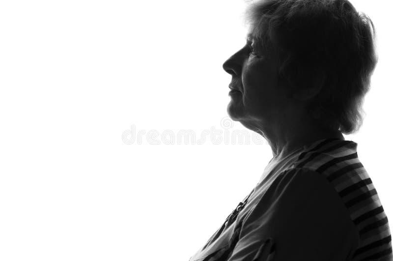 一名老哀伤的妇女的剪影 免版税库存图片