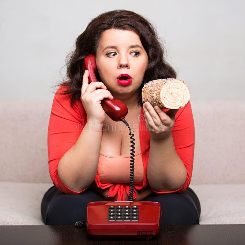 一名肥胖妇女的画象有电话的和а结块 免版税库存图片