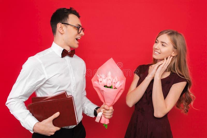 一名英俊的学生,戴着眼镜,给一件礼物和一花束他的女朋友反对红色背景 免版税库存照片