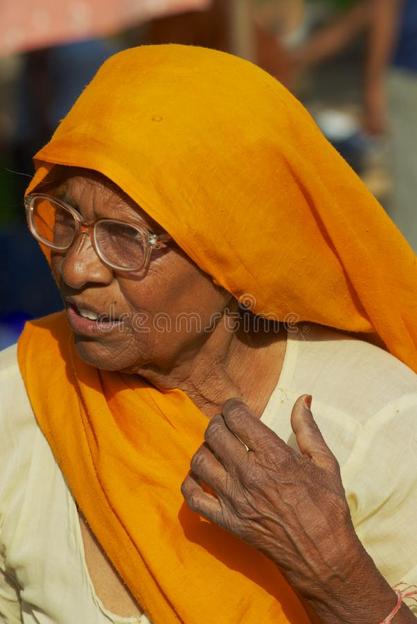一名资深妇女戴着眼镜和橙色头巾的画象在街道在斋浦尔,印度 免版税库存图片
