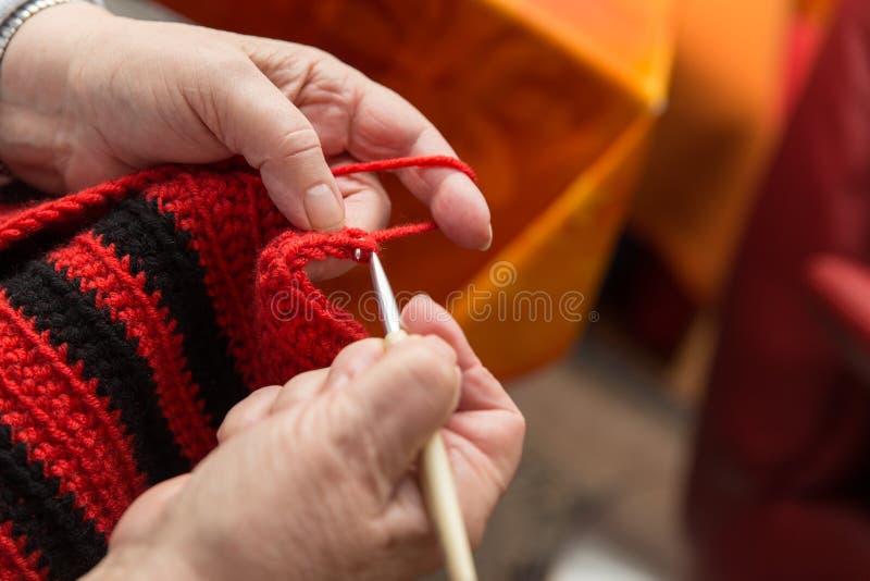 从一名资深妇女的特写镜头手有钩针和羊毛的 库存照片
