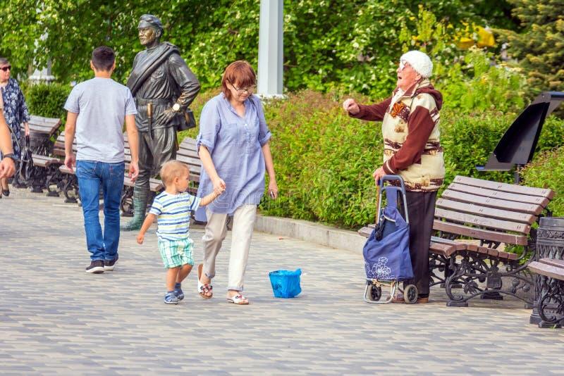 一名赤贫年长妇女请求在堤防的施舍在雕塑附近给红军战士苏霍夫 库存照片