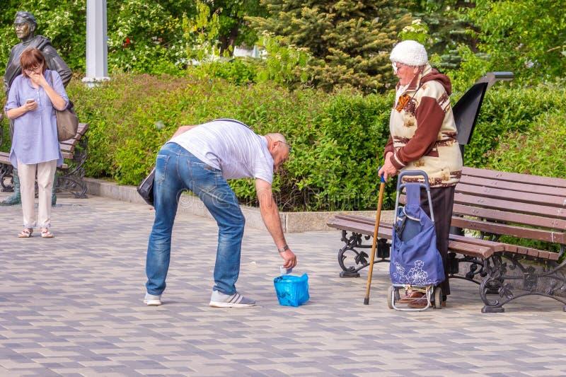 一名赤贫年长妇女请求在堤防的施舍在雕塑附近给红军战士苏霍夫 免版税库存照片