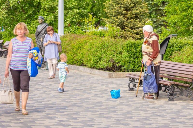 一名赤贫年长妇女请求在堤防的施舍在雕塑附近给红军战士苏霍夫 免版税图库摄影