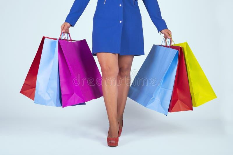 一名身穿蓝色连衣裙的女士和一双红色鞋子,在浅蓝色背景上拿着彩色的孤立购物袋 库存照片