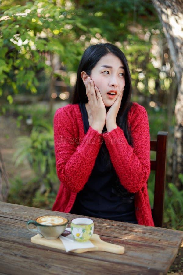 一名震惊妇女的画象坐桌用在的咖啡 图库摄影