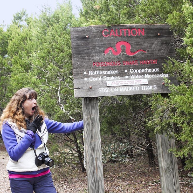 一名震惊的妇女读一个足迹小心标志 库存图片