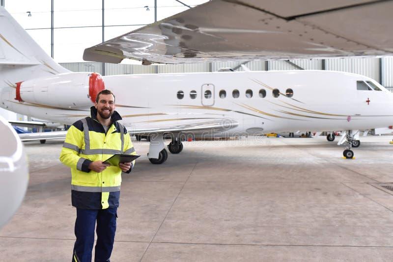 一名飞机机械员的画象在有喷气机的一个飞机棚在ai 库存照片