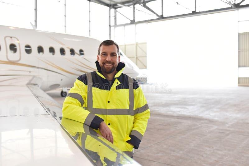 一名飞机机械员的画象在有喷气机的一个飞机棚在ai 免版税库存照片