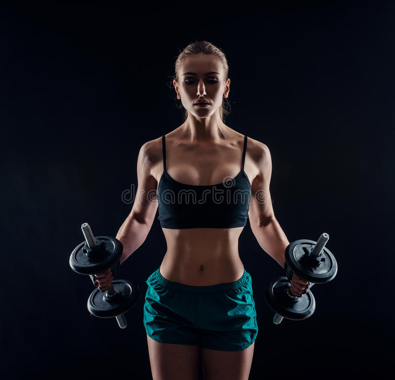 一名年轻健身妇女的画象做与哑铃的运动服的锻炼在黑背景 被晒黑的性感的运动女孩 免版税库存照片