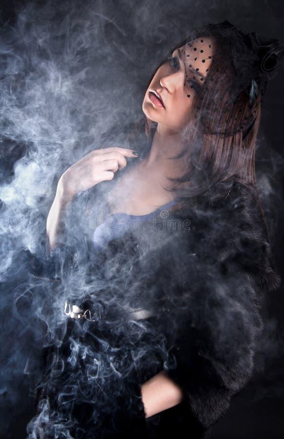 一名年轻可爱的妇女的画象一阵烟幕的 库存图片