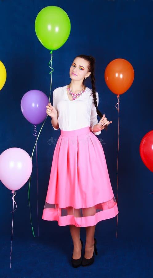 一名年轻可爱的妇女的画象在许多明亮的气球附近的 库存照片