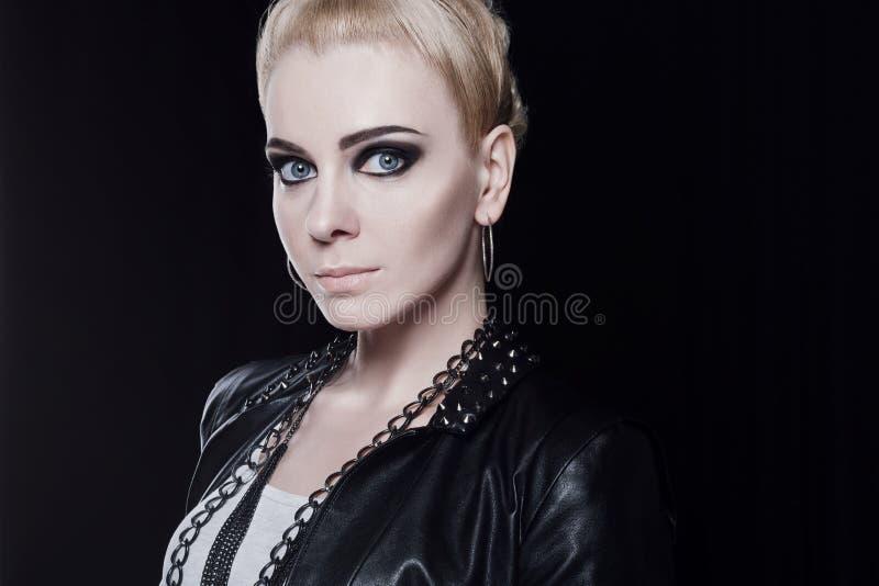 一名年轻可爱的白肤金发的妇女的画象皮夹克的 免版税库存照片