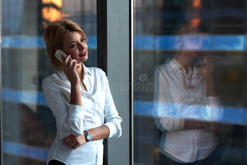 一名年轻女实业家的画象谈话在手机 免版税库存照片