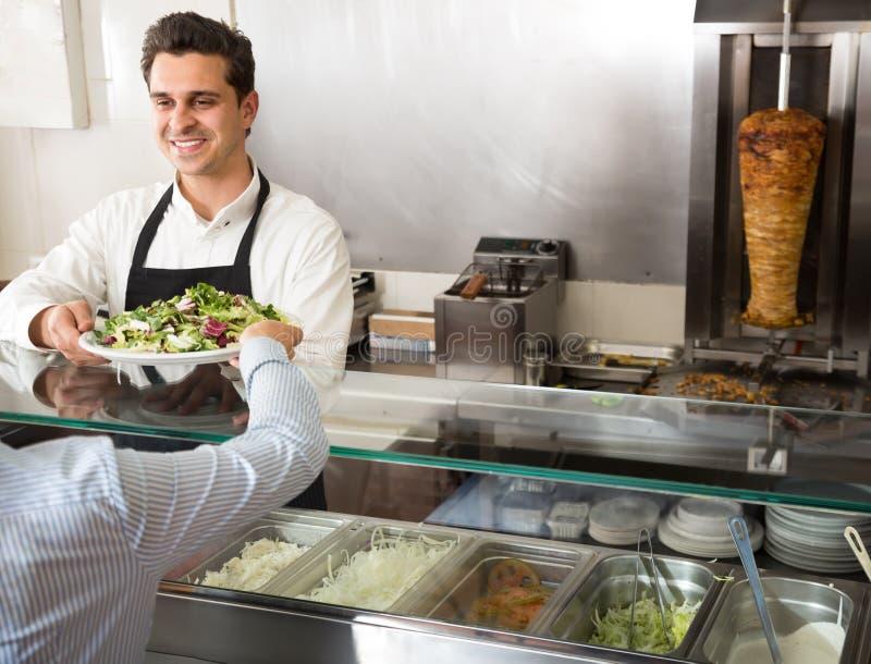 一名年轻男性快餐工作者的画象柜台的 免版税图库摄影