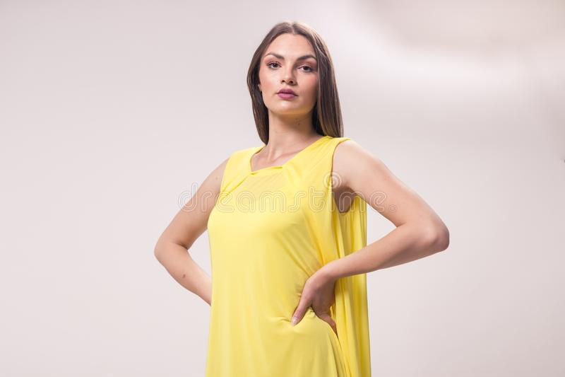 一名年轻白种人妇女,演播室,白色背景,黄色dres 免版税库存照片