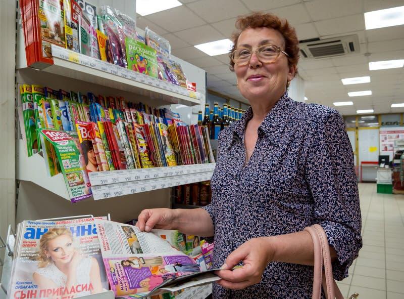 一名年长妇女在商店支持与杂志的窗口 库存照片
