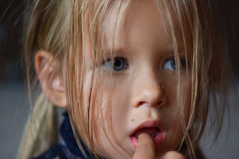 一哀伤的浪漫女孩的画象有大蓝眼睛和一个手指的在她的从东欧的嘴,特写镜头,黑暗的背景 免版税库存照片