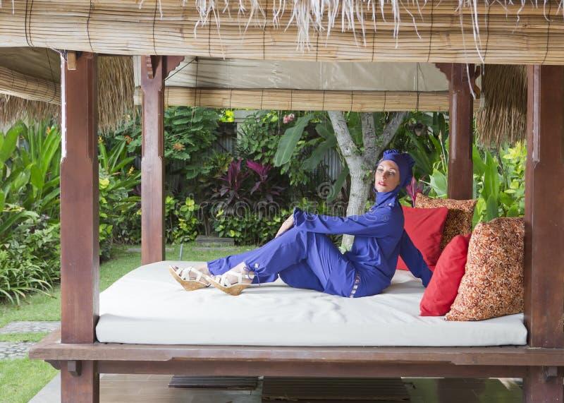 一回教游泳衣burkini的可爱的妇女在休息的眺望台在庭院里 免版税库存照片