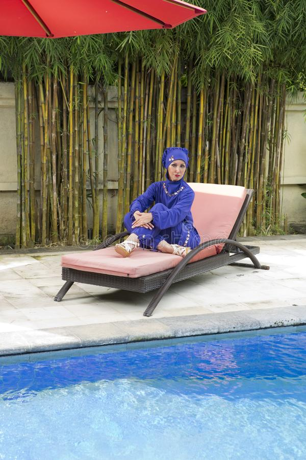 一回教游泳衣burkini的可爱的妇女在水池附近的一张海滩板条床上 免版税库存图片