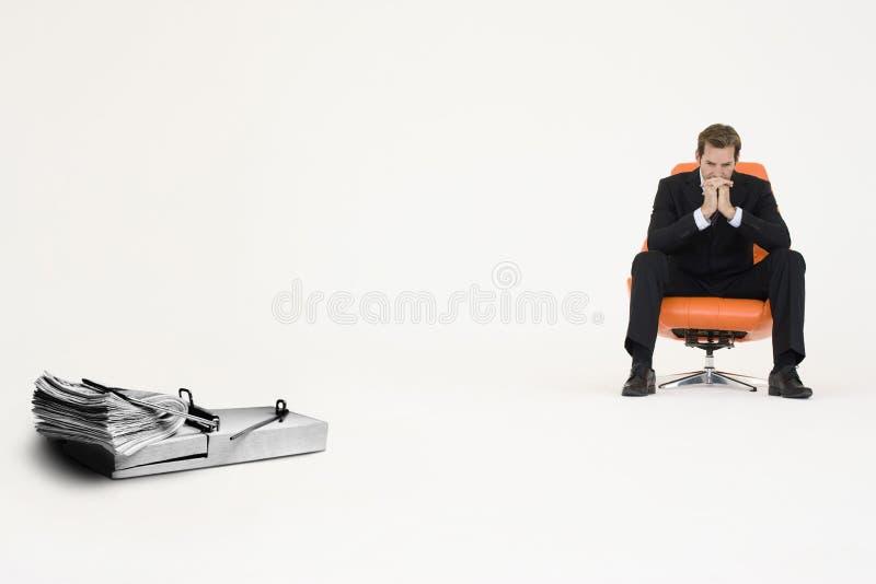 一团在老鼠陷井的现金与在代表财政困难的椅子的沉思商人 图库摄影