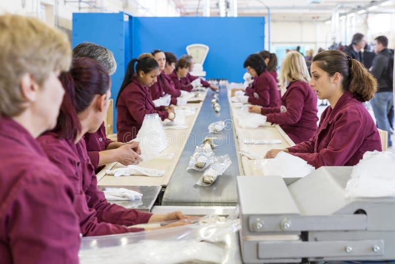 一团装配线的工作者在军火工厂 免版税库存照片