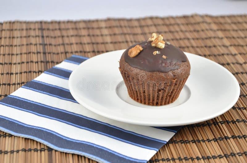 一在白色板材的褐巧克力色松饼用餐巾最佳的点心 库存图片