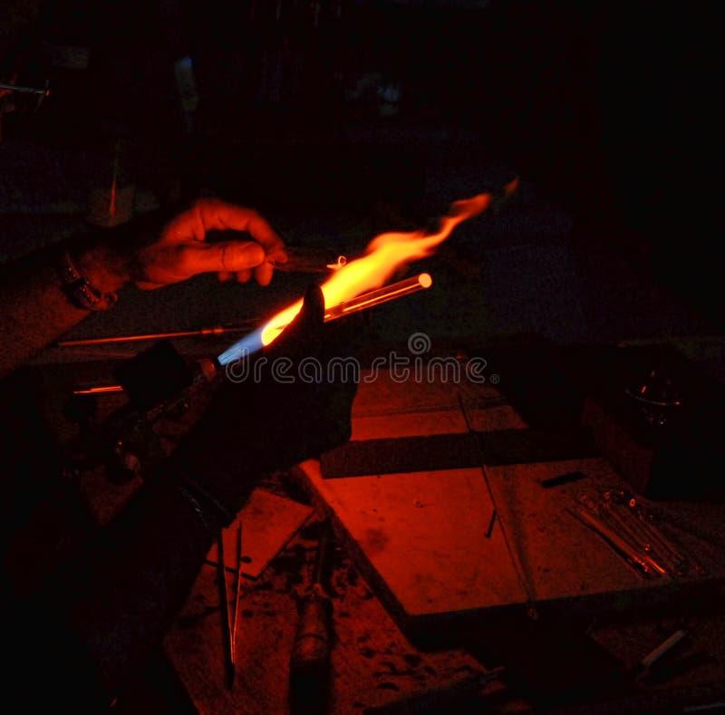 一块吹玻璃器运作的玻璃的手在明火的 免版税库存图片