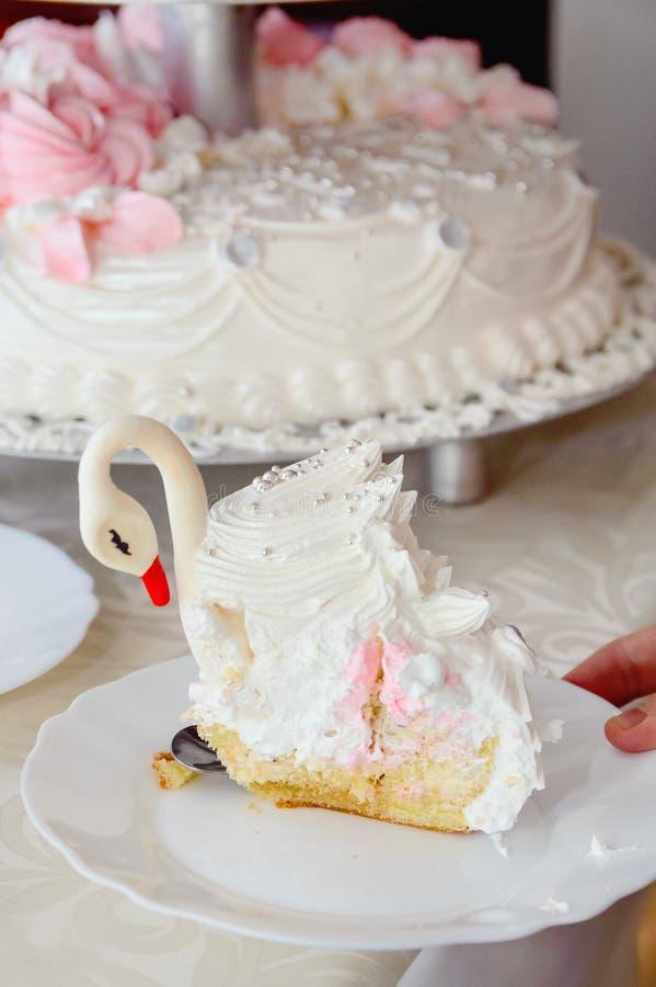 一块婚宴喜饼的片断以天鹅的形式在板材说谎 E 免版税库存图片