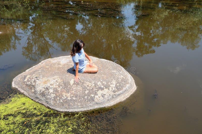 一块巨大的石头的少妇 库存图片