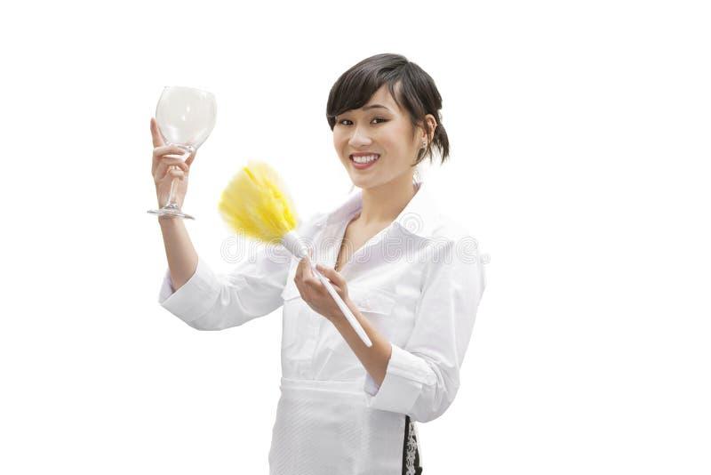 一块愉快的女性房子擦净剂拂去的灰尘的玻璃的画象与羽毛喷粉器的在白色背景 免版税图库摄影