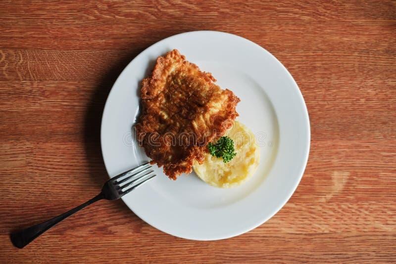 一块板材用土豆泥和一个敬酒的鸡蛋用蕃茄和叉子 顶视图 免版税库存图片