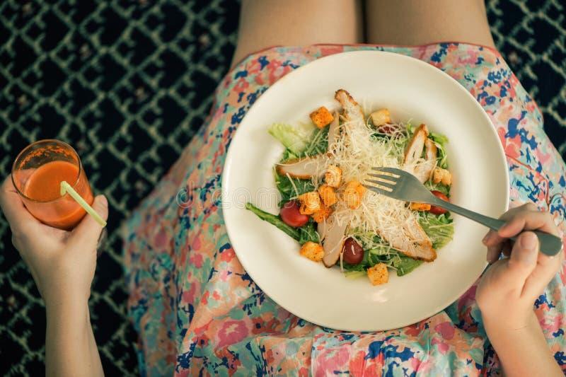一块板材用在女性膝盖的沙拉和杯红萝卜汁 在视图之上 食物和健康生活方式的概念 免版税库存图片