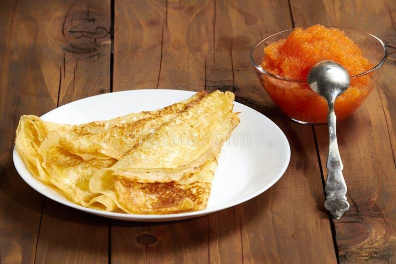 一块板材用薄煎饼和一个碗用鱼子酱在桌上 库存图片