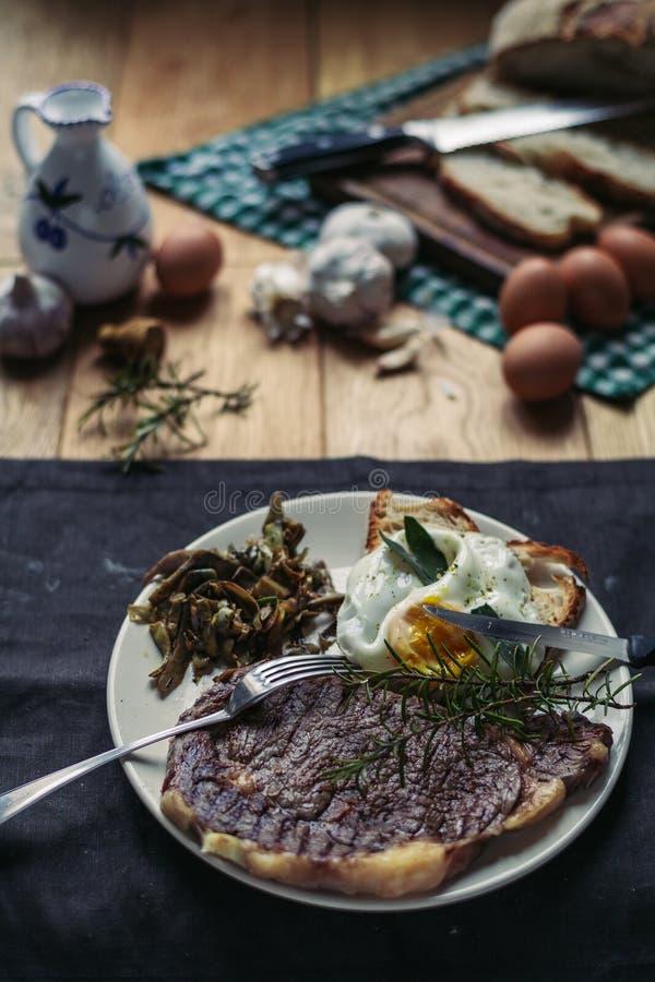 一块烤牛排和面包片用刀子、鸡蛋、迷迭香、橄榄油和大蒜切开了 免版税库存图片